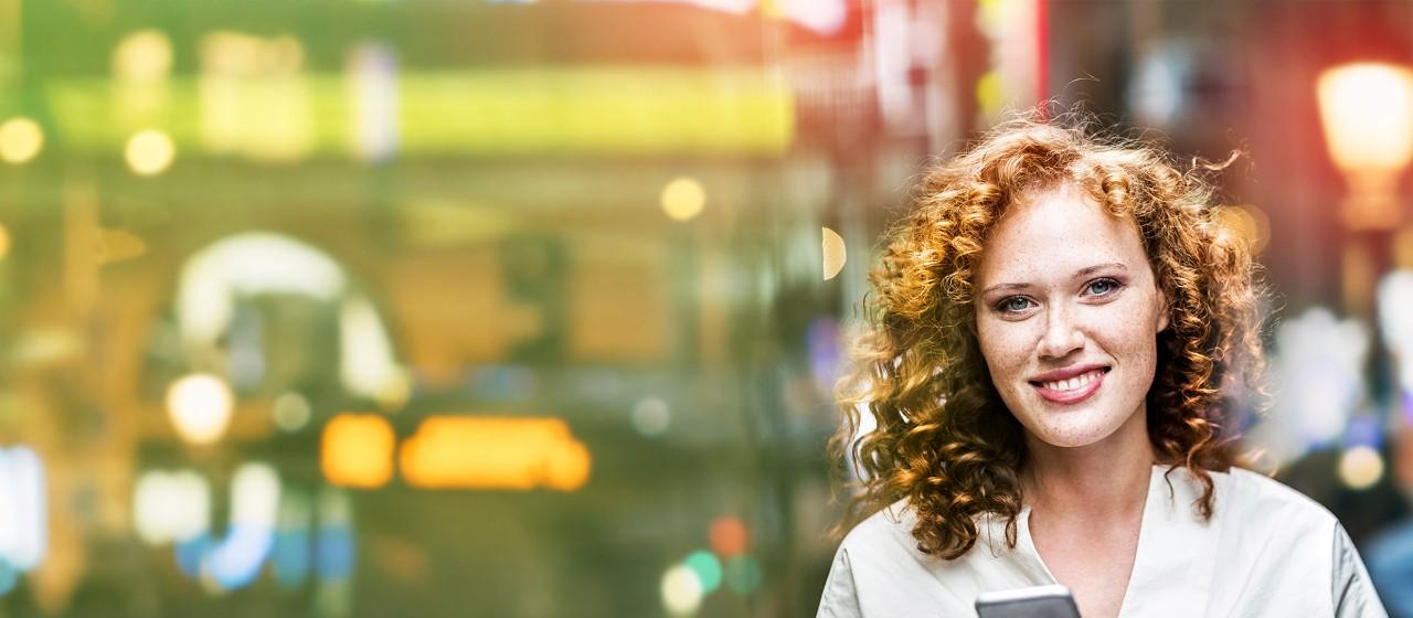 Lächelnde, junge Frau in der Innenstadt.
