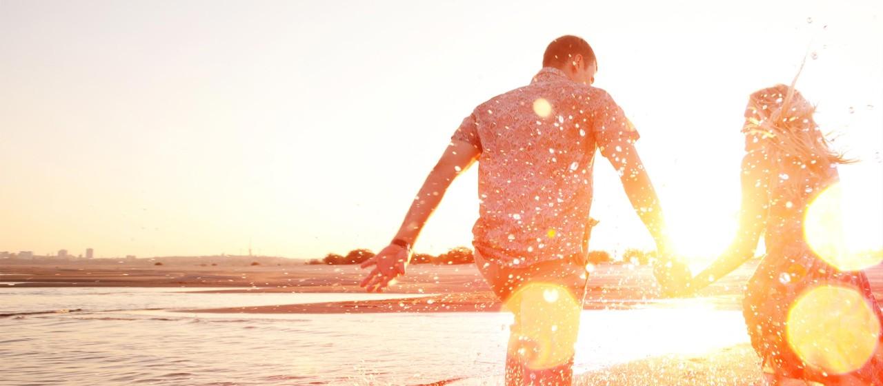 Junges Paar rennt am Strand durch das Wasser.