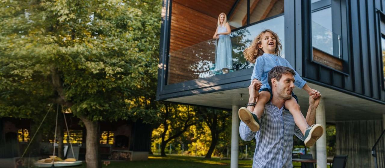Junge Frau mit Kaffeetasse schaut aus dem Fenster.