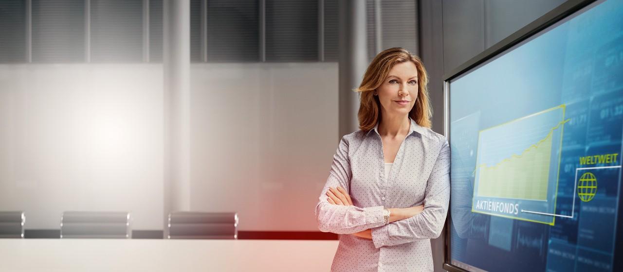 Eine Frau steht vor einem Fernseher.