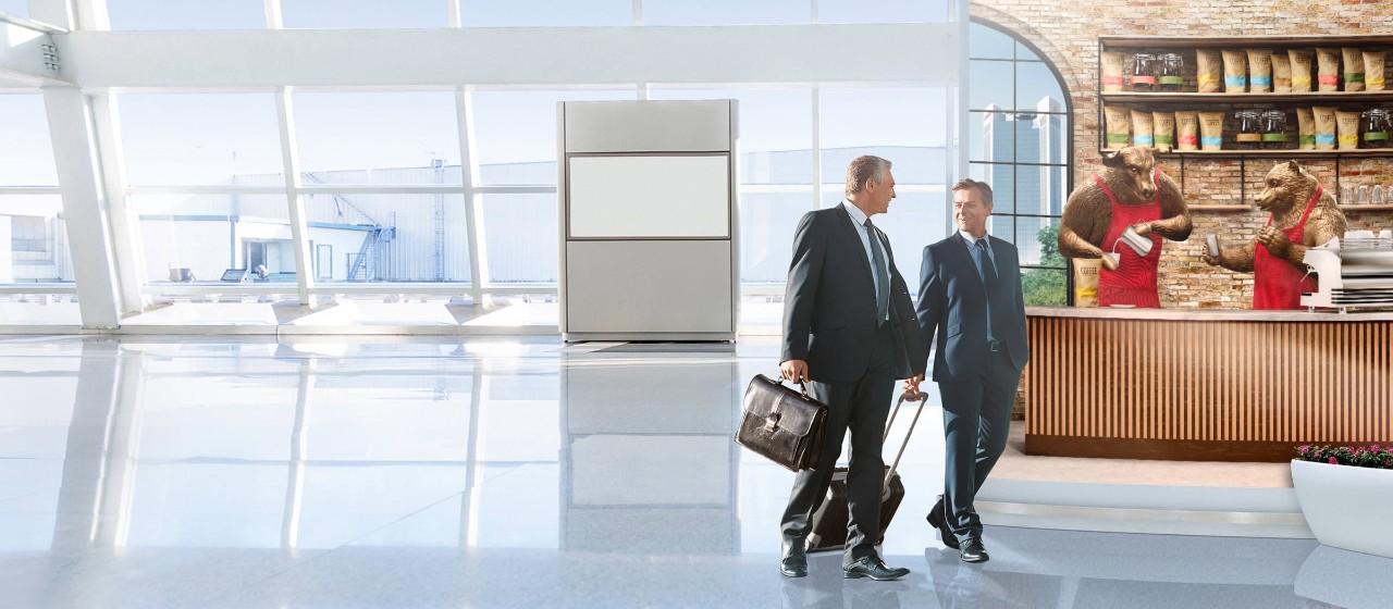 Zwei Männer im Anzug gehen gemeinsam durch eine Eingangshalle.