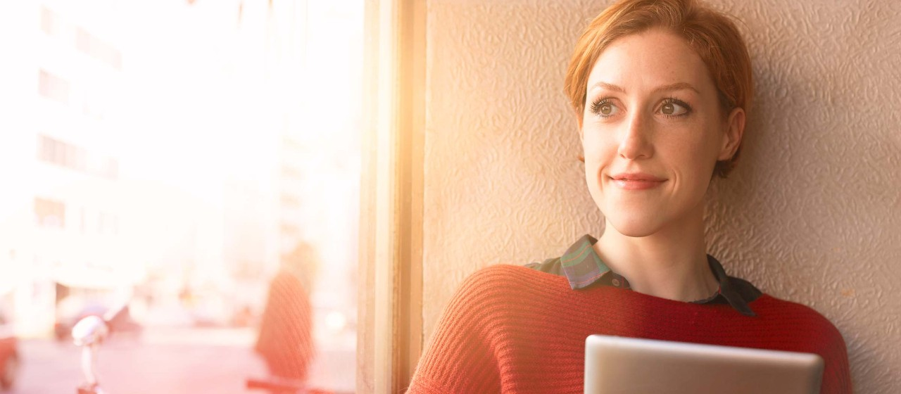 Junge Frau mit Tablet in der Hand sitzt an einem Fenster
