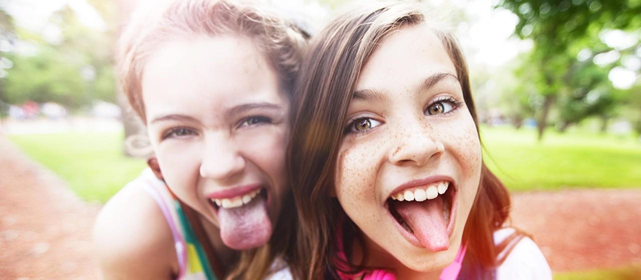 Zwei junge Mädchen, die die Zunge rausstrecken.