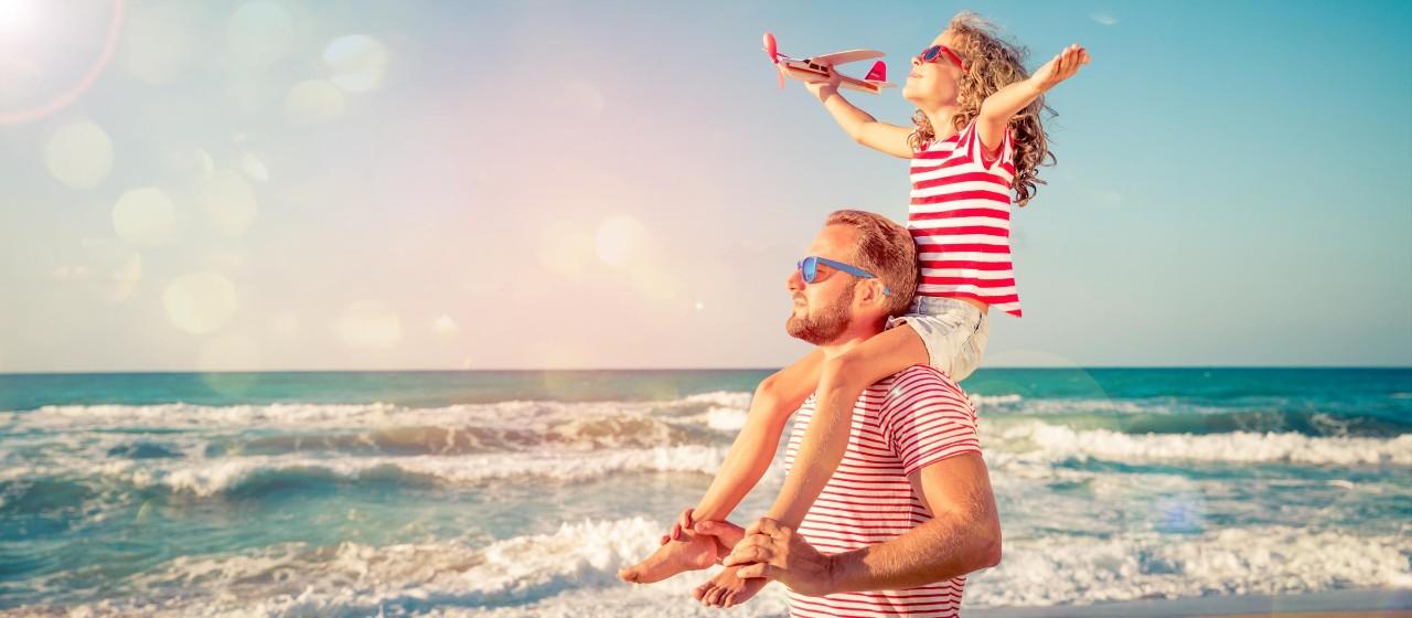 Vater mit Tochter auf den Schultern am Strand.