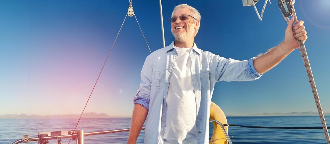 Mann steht auf einer Segelyacht.