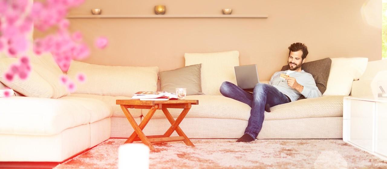 Mann sitzt mit einer Kreditkarte und Notebook auf dem Sofa.