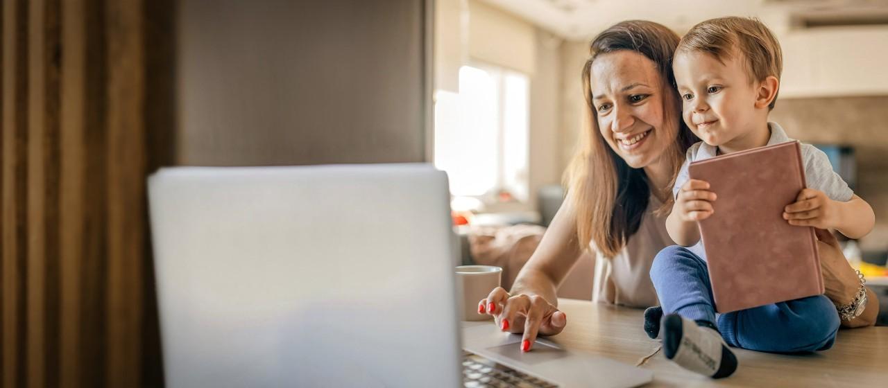 Ein junger Mann schaut am Esstisch sitzend auf ein Tablet.