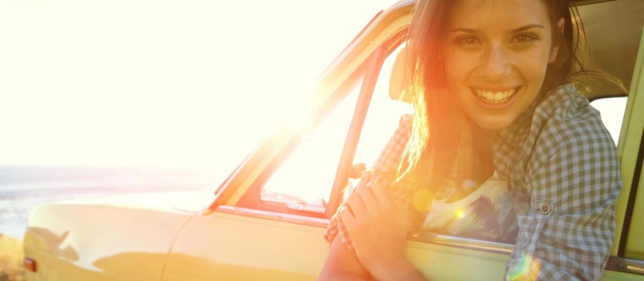 Junge Frau schaut lächelnd aus einem Autofenster.