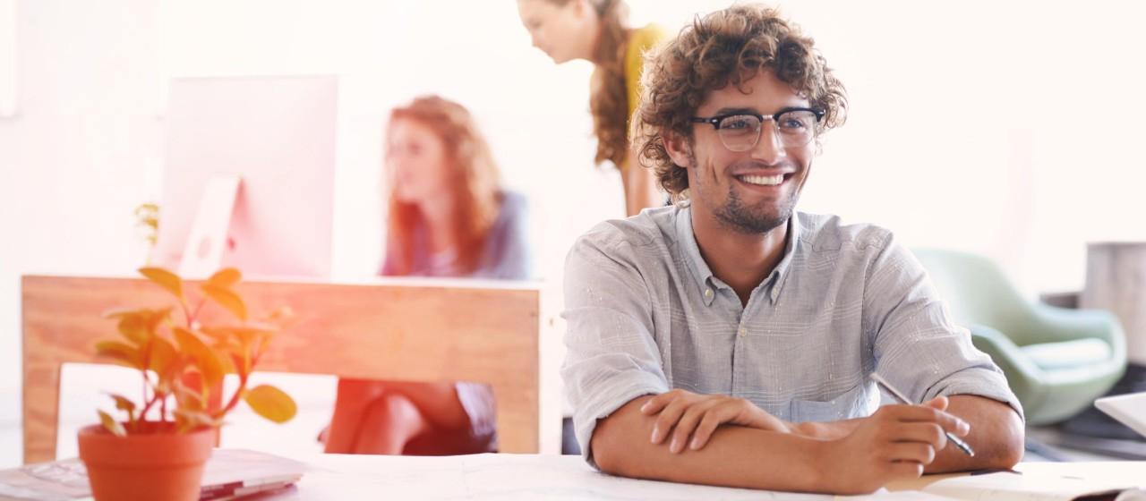Junger Mann sitzt am Schreibtisch.
