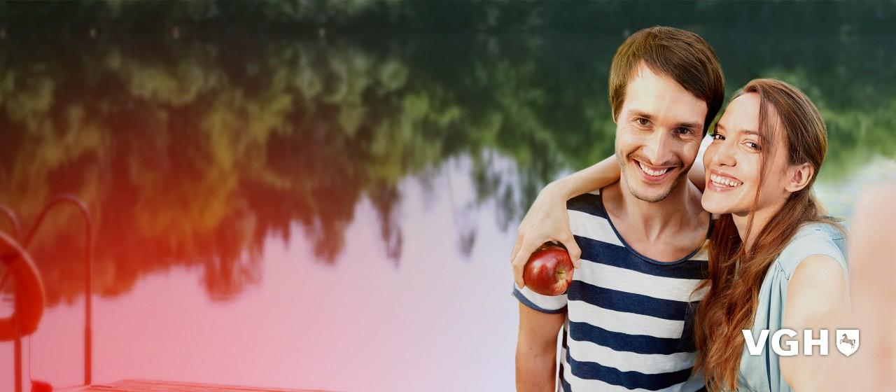 Junges Pärchen mit einem Apfel in der Hand lächeln in die Kamera.