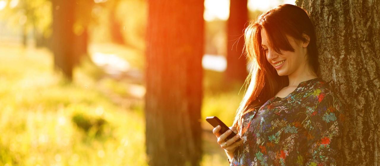 Frau mit Handy im Park