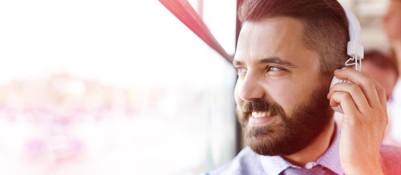Lächelnder Mann mit Kopfhörern im Bus.